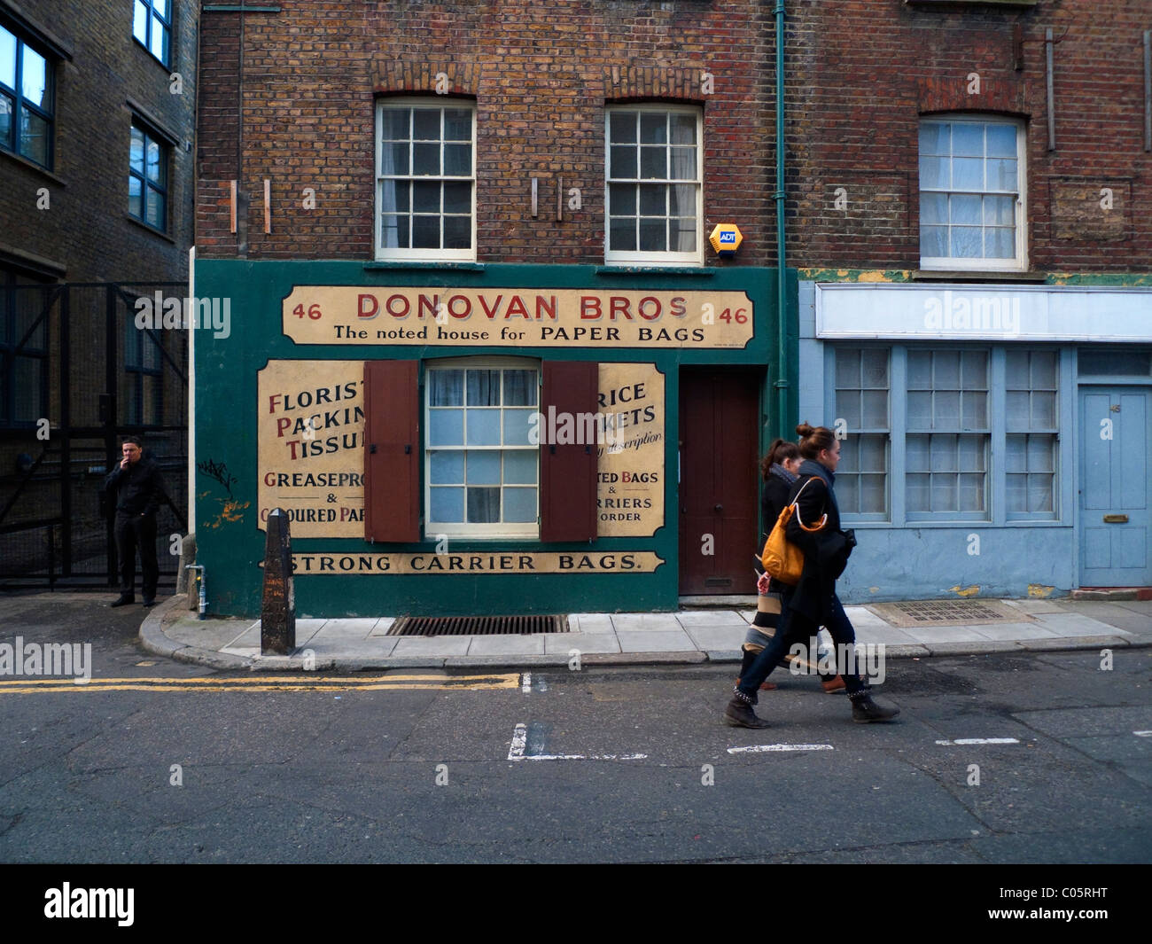Two young women walking past Donovan Bros Paper Bag shop in Spitalfields East London UK KATHY DEWITT - Stock Image