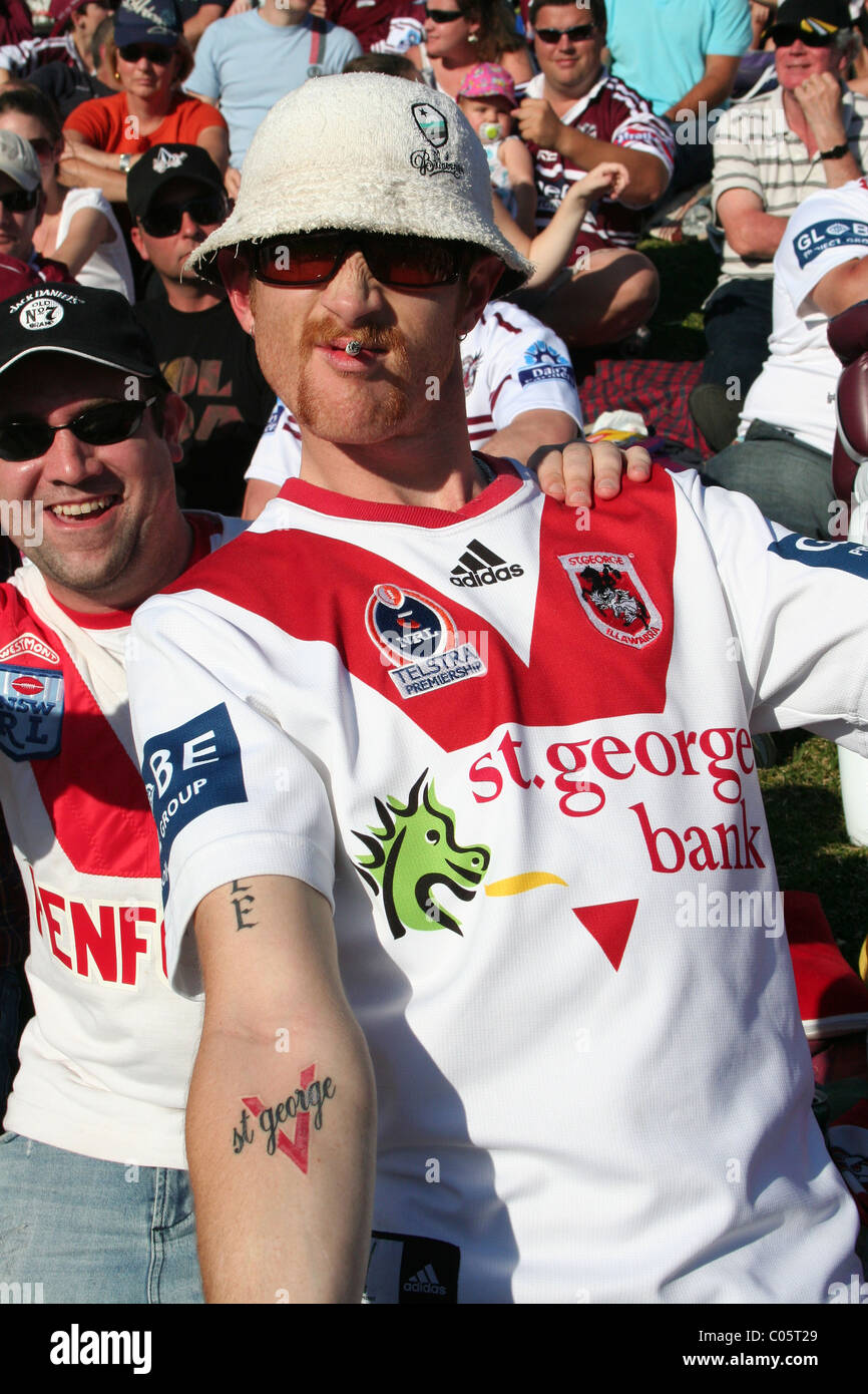 A St George supporter (NRL) displays his loyalty to his team with a tattoo of the team's name on his arm - Stock Image