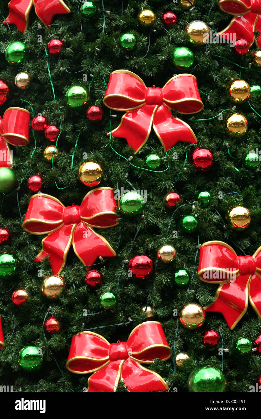 Red bows and Christmas decorations on Christmas tree - Stock Image