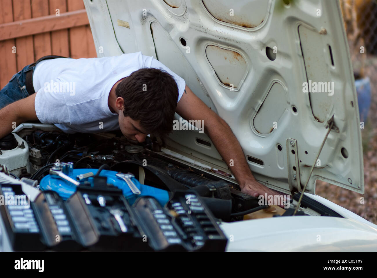 Man working on car in yard. Do it yourself mechanic performing auto repair. Examining engine compartment for signs - Stock Image