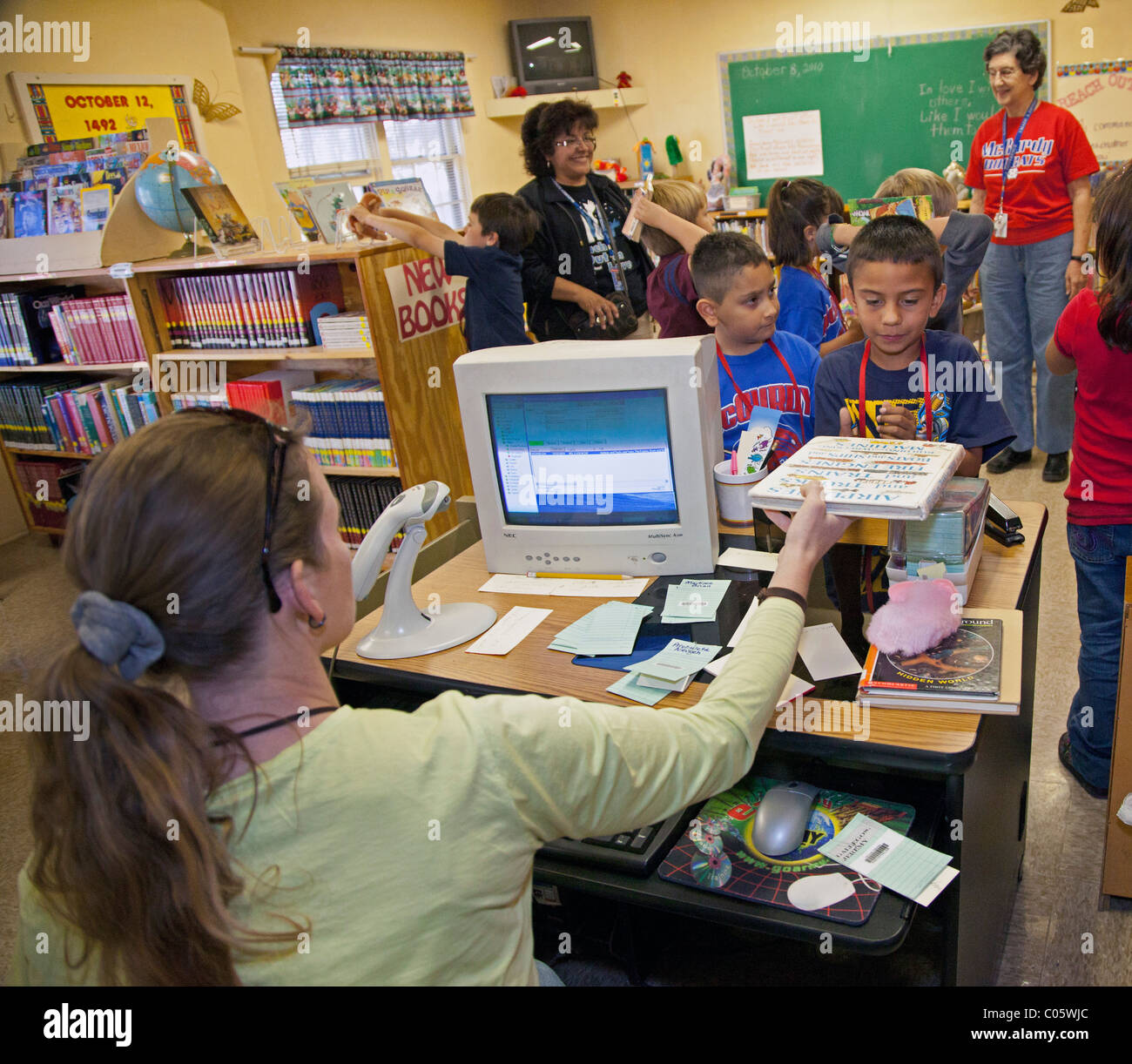 Children Check Out Books at School Library - Stock Image