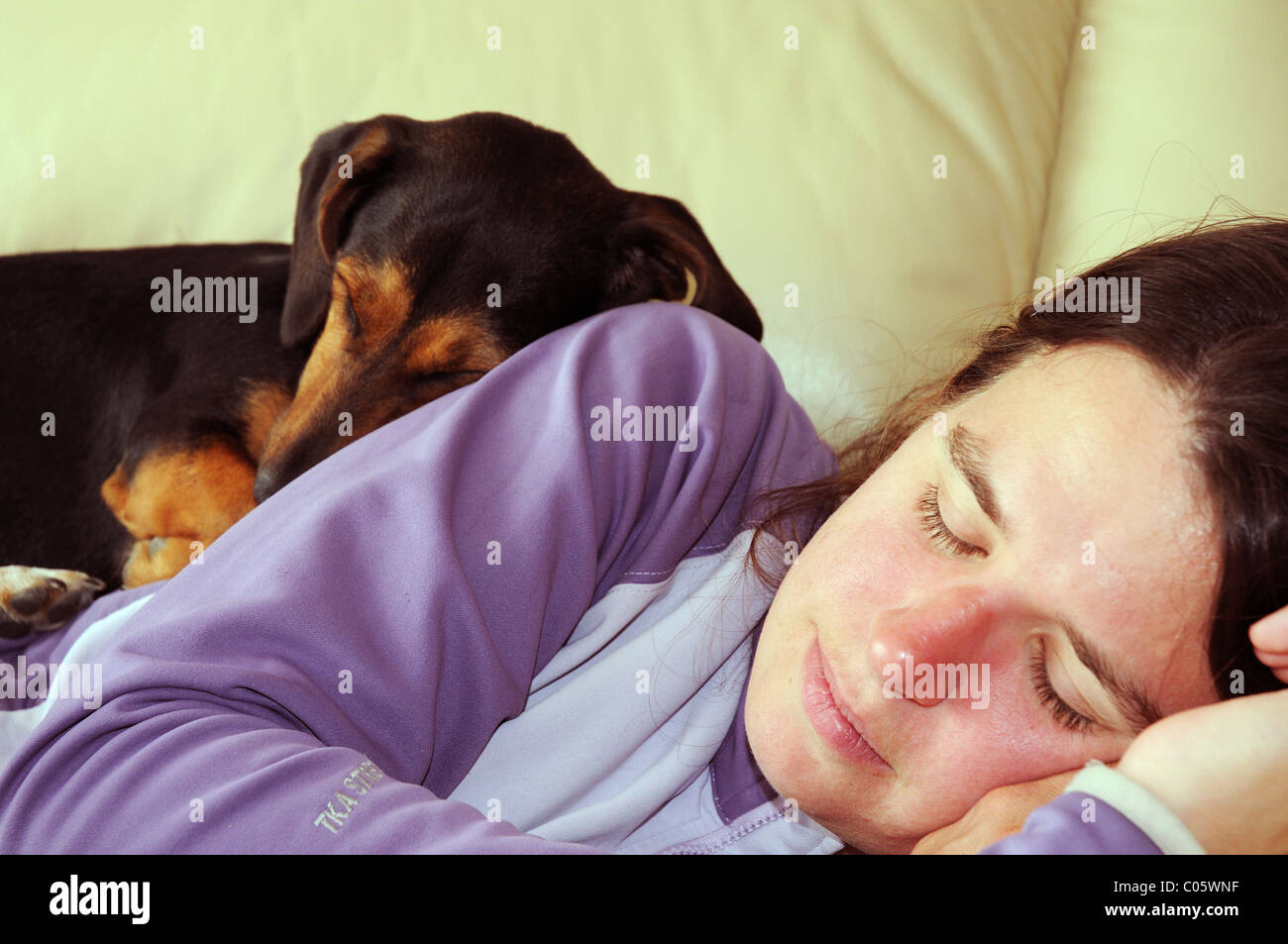 A dog curled up asleep on a sleeping woman - Stock Image