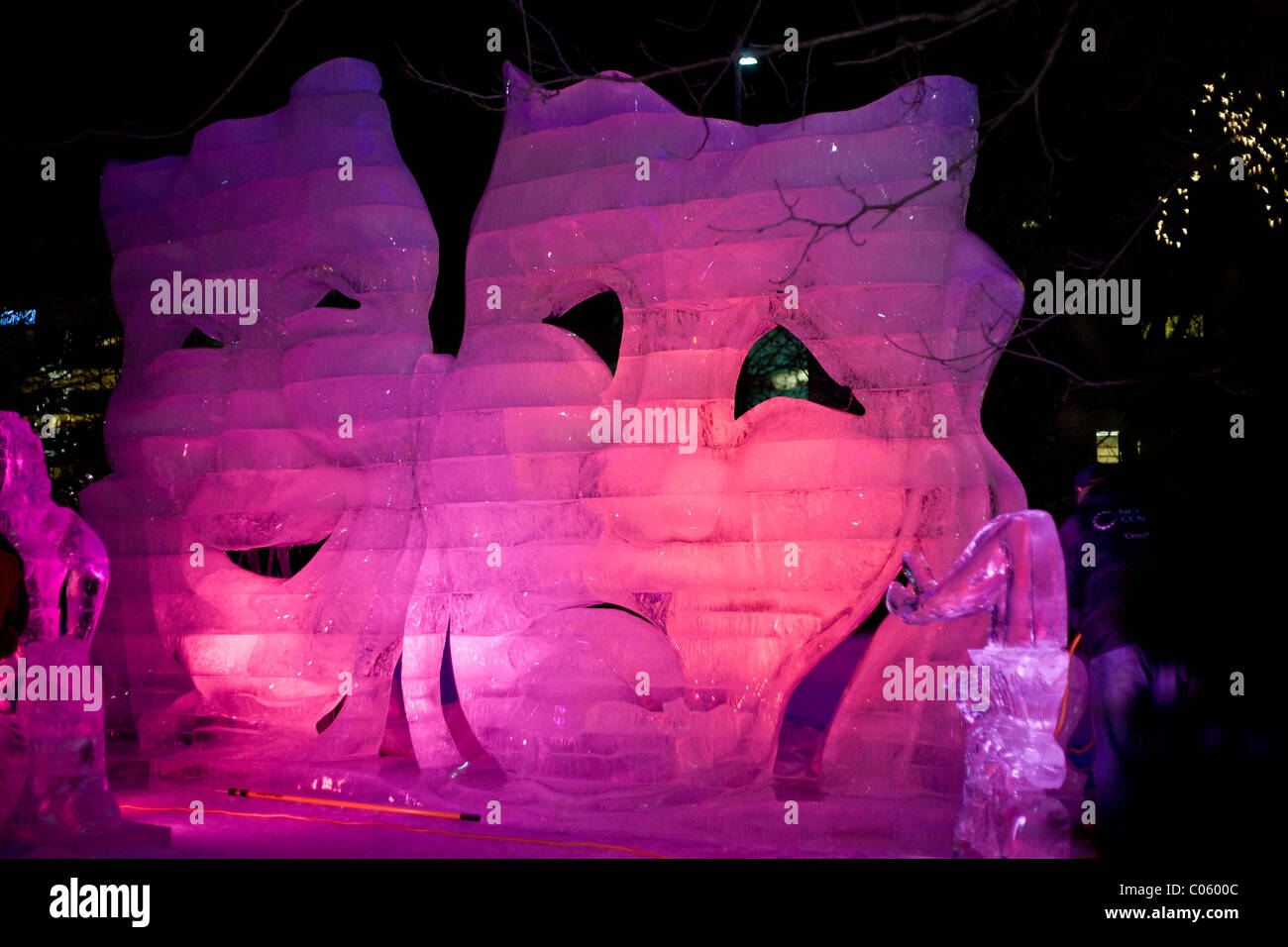Comedy and Tragedy in Red Ice . An ice sculpture of the famous masks at night, backlit with red and blue LED lamps - Stock Image