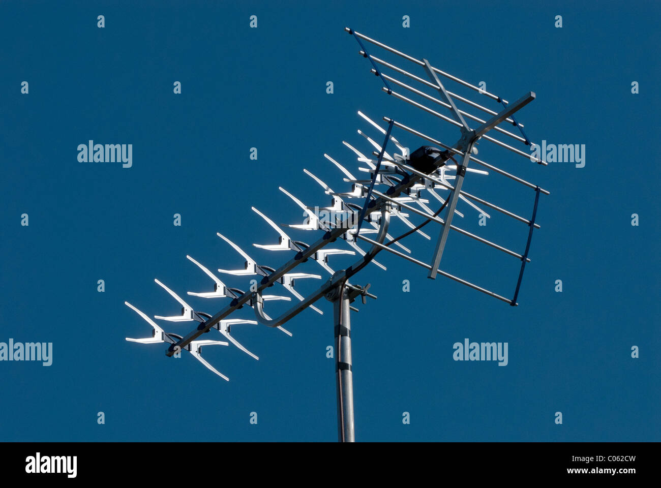 A television aerial or antenna against a plain blue sky.  A good aerial is required for the UK digital switchover. - Stock Image