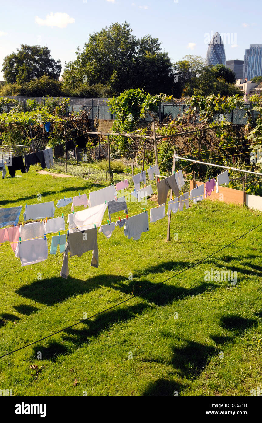 UK.Clothes dry in the sun in a garden near the Spitalfields City Farm, with views of City in background, in east - Stock Image