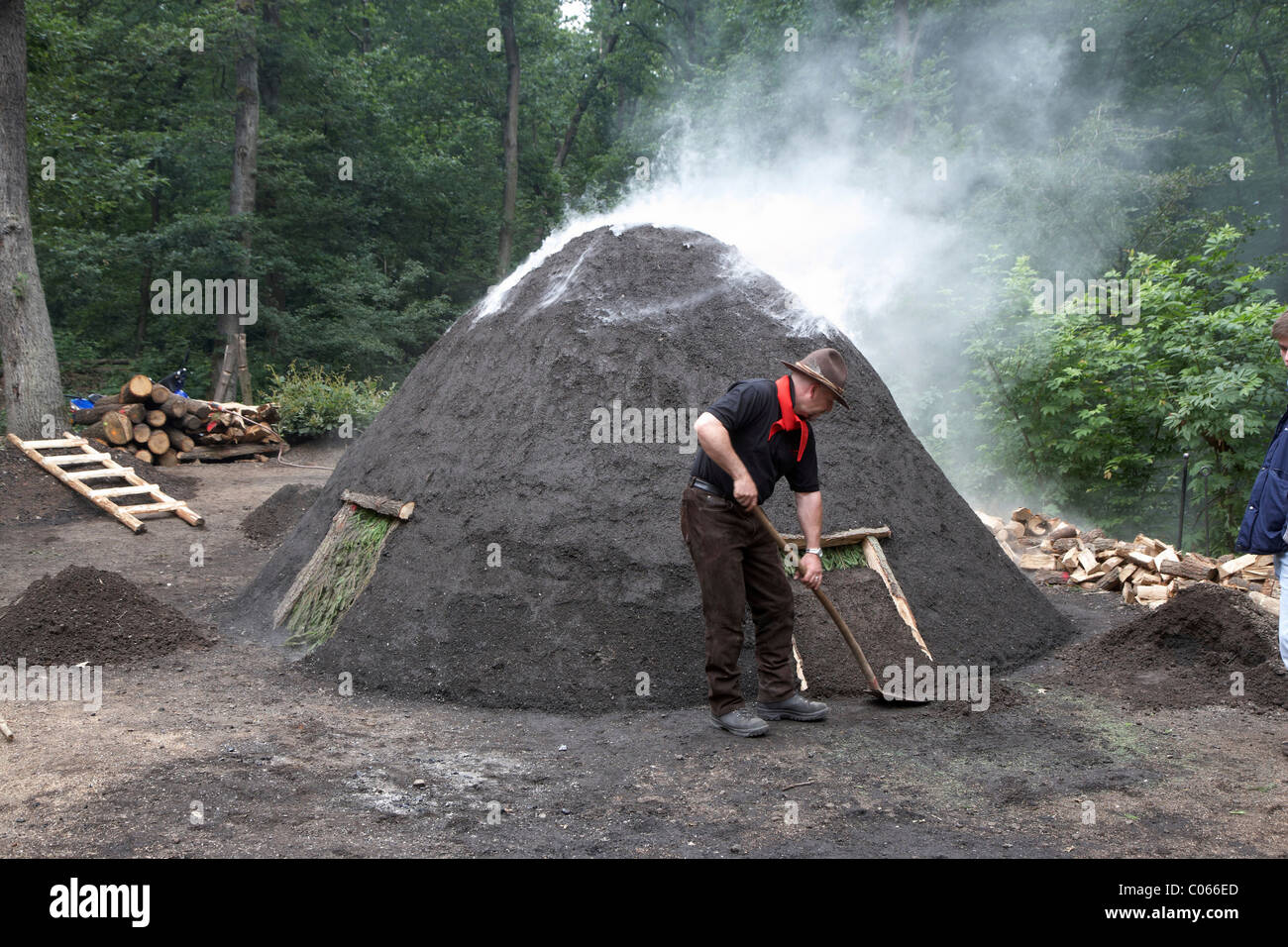 Charburner working on a charcoal kiln, demonstration during the Koehlertage or charcoal burner days Boppard for - Stock Image