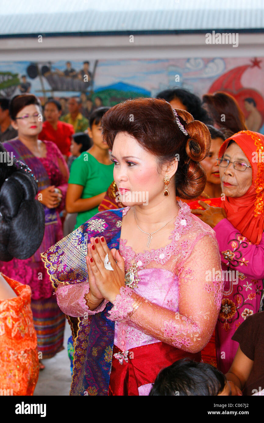 Woman with her hands held together, guests at a wedding ceremony, Siantar, Batak region, Sumatra, Indonesia, Asia - Stock Image