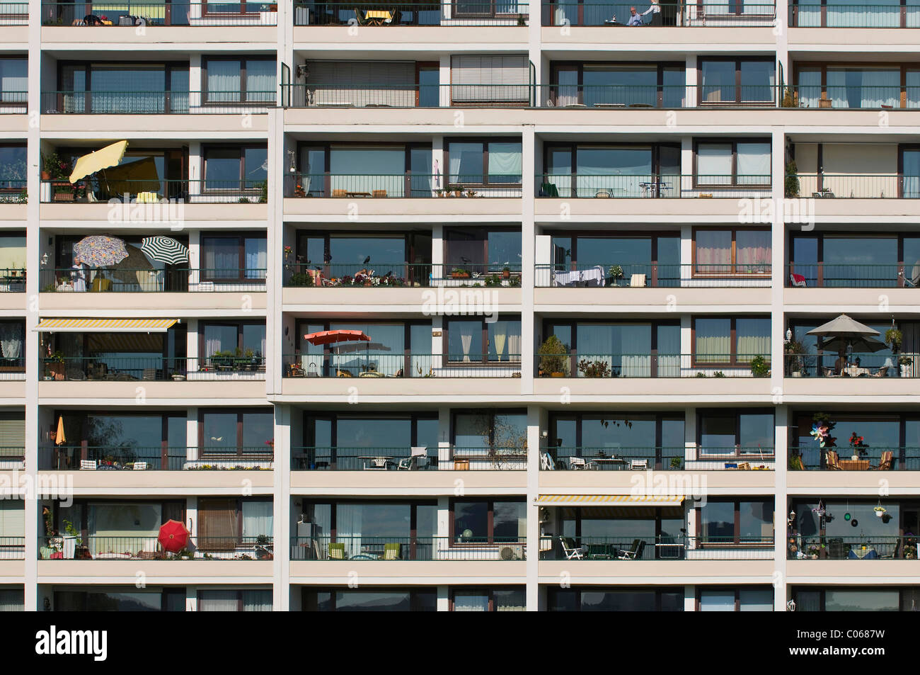 House facade, many balconies with parasols and furniture - Stock Image