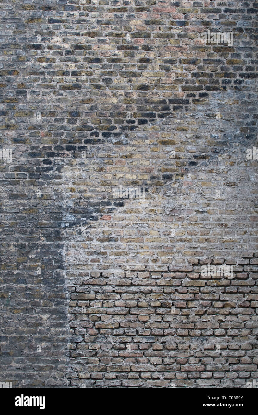 Brick wall with traces of earlier buildings, two roof ridges and plaster remains on the former building walls, background Stock Photo