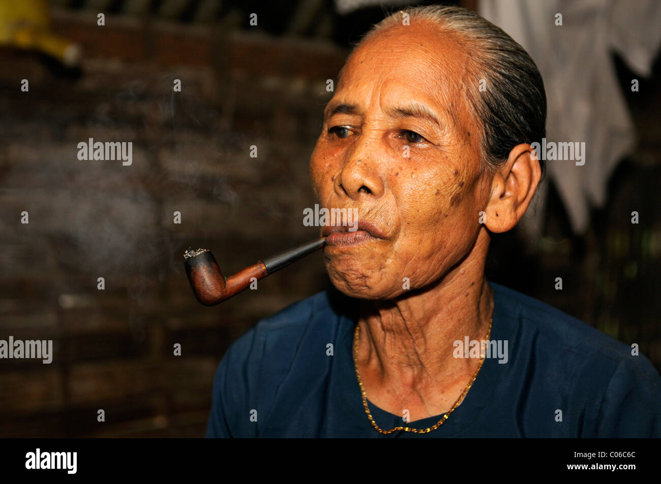 Old woman smoking a pipe, Vietnam, Asia - Stock Image