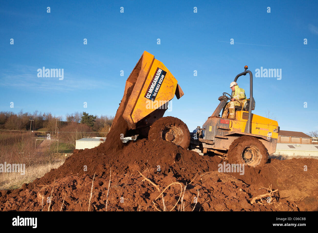 Dump truck emptying its bucket full of earth - Stock Image