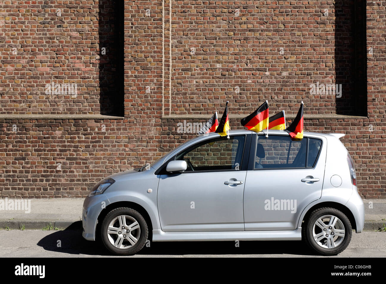 Small car decorated with five Germany flags, World Cup, Krefeld-Uerdingen, North Rhine-Westphalia, Germany, Europe - Stock Image