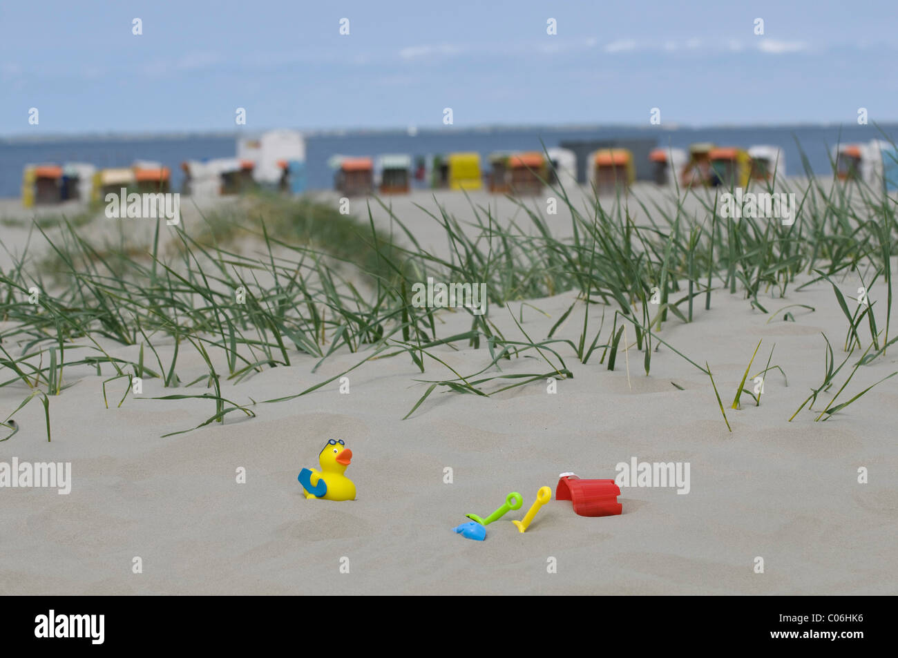 Holidays, children's toys on a sand dune in front of roofed wicker beach chairs on a beach and the sea, Norddeich, - Stock Image
