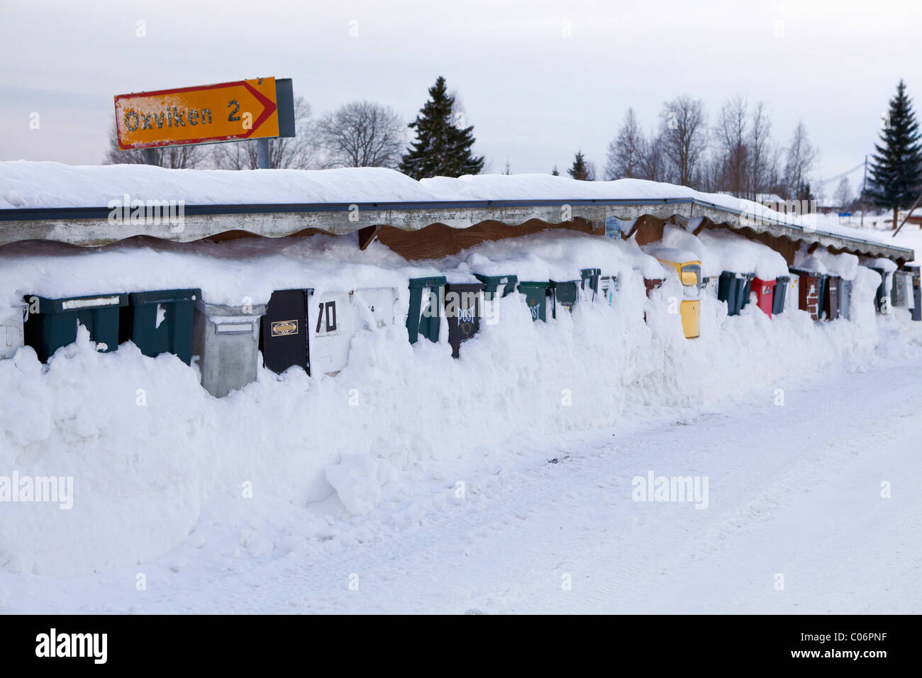 Postboxes snowed in by snow covered road - Stock Image