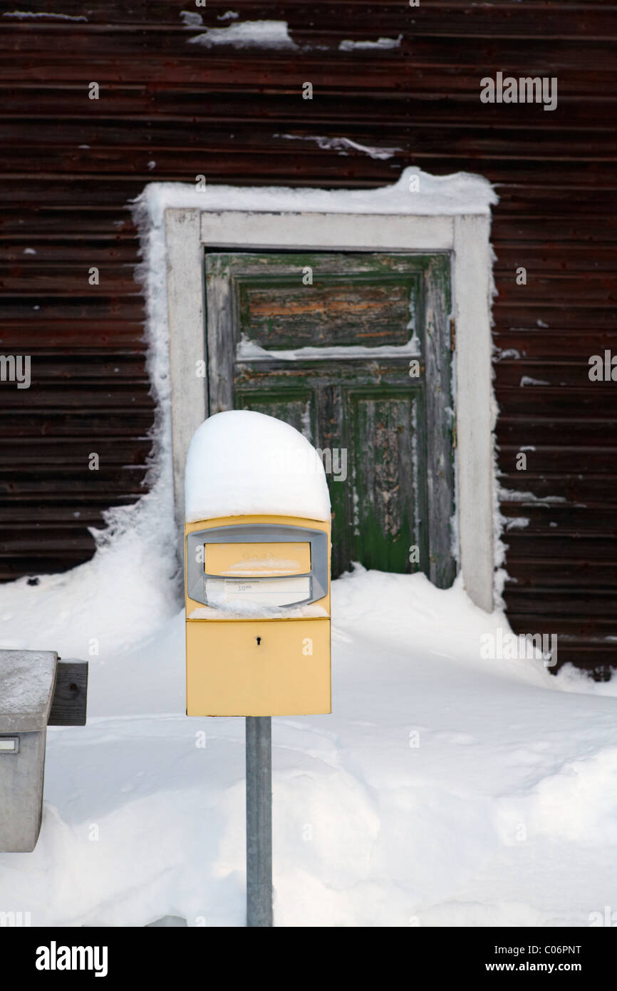 Postbox covered in snow next to rural house - Stock Image
