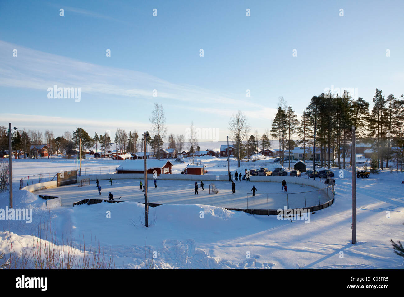 People ice-skating in outside ice rink in rural small town covered in snow - Stock Image