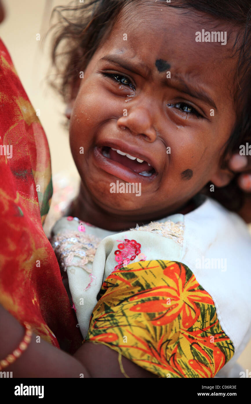 girl crying in the arms of her mother Andhra Pradesh South India - Stock Image