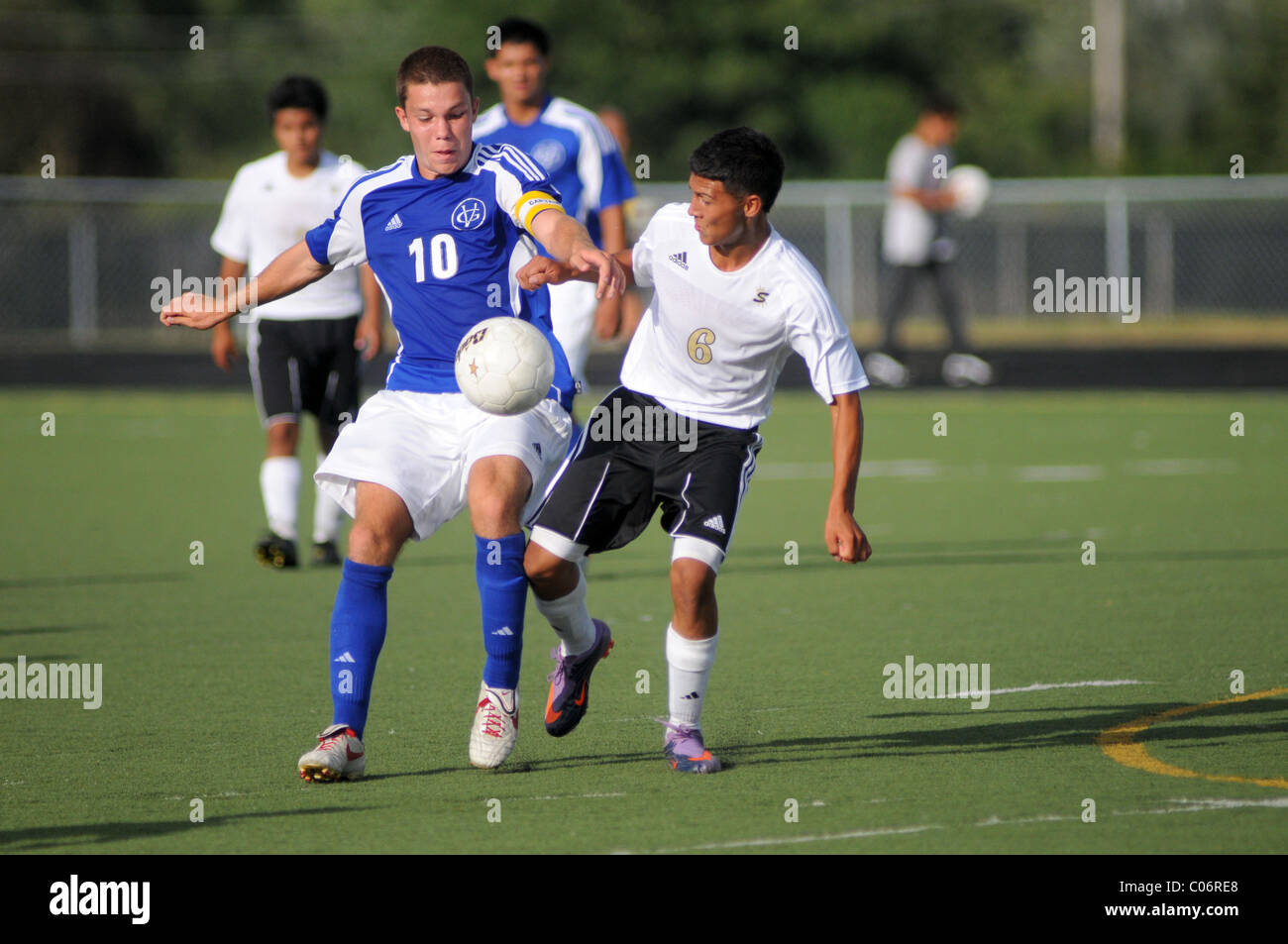 Players battle for possession of the ball during a high school soccer match. USA. - Stock Image