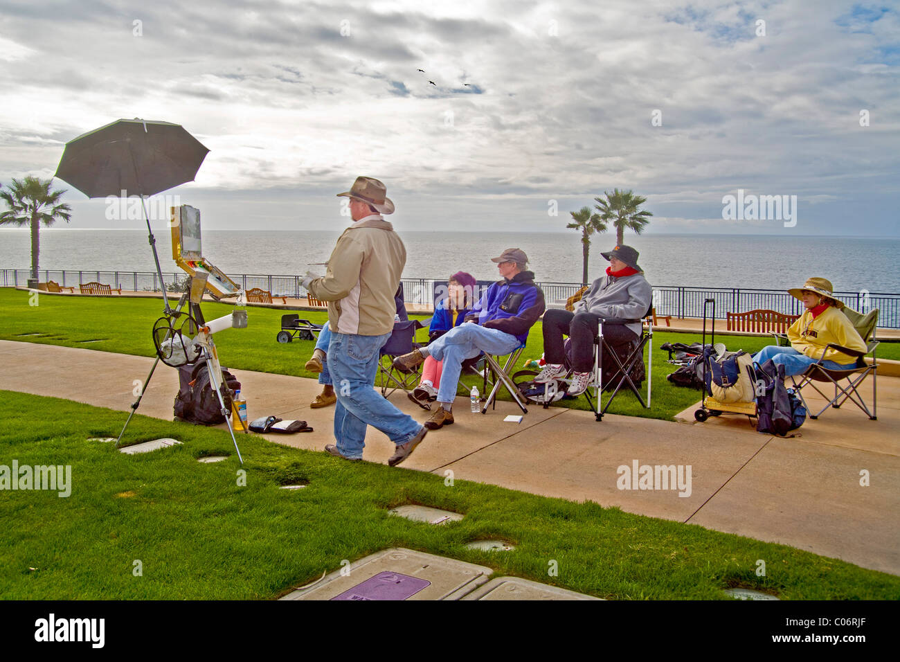 With his easel standing beside learn learning culture cul a plein air artist demonstrates oil painting while his - Stock Image