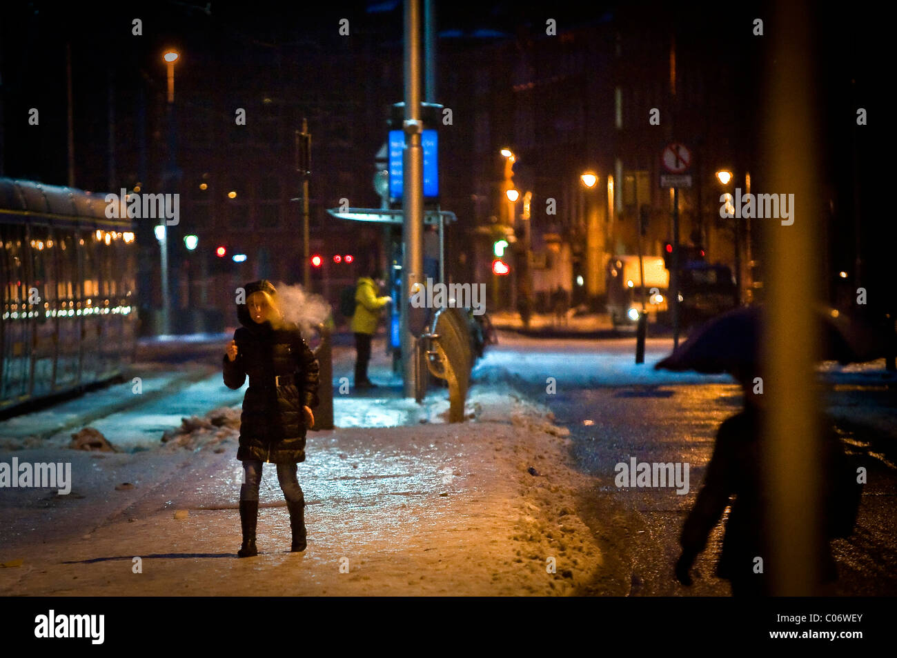 A woman smoking a cigarette tentatively walks across compacted snow and ice at a tram stop in Dublin city centre, - Stock Image