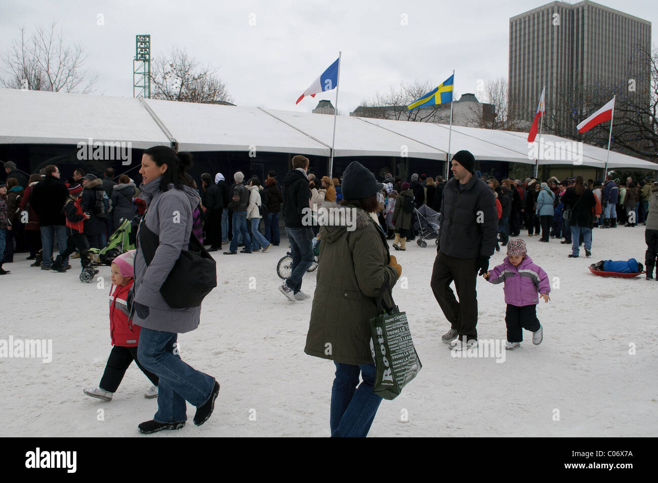 Onlookers watch professional ice carvers at Confederation Park during the first weekend of Winterlude Festivities - Stock Image