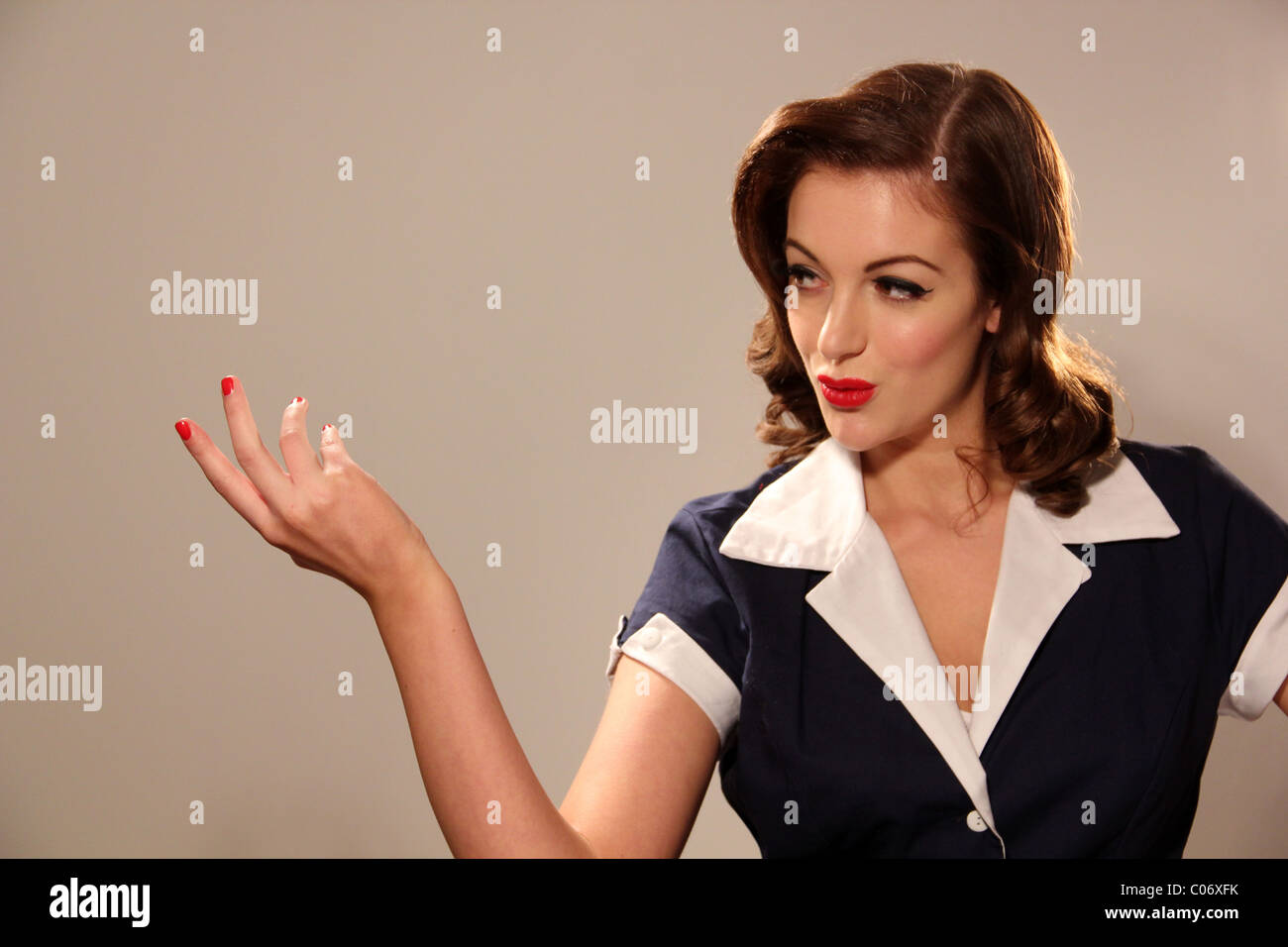 Woman in 1950s clothing pointing to an imaginary object - Stock Image