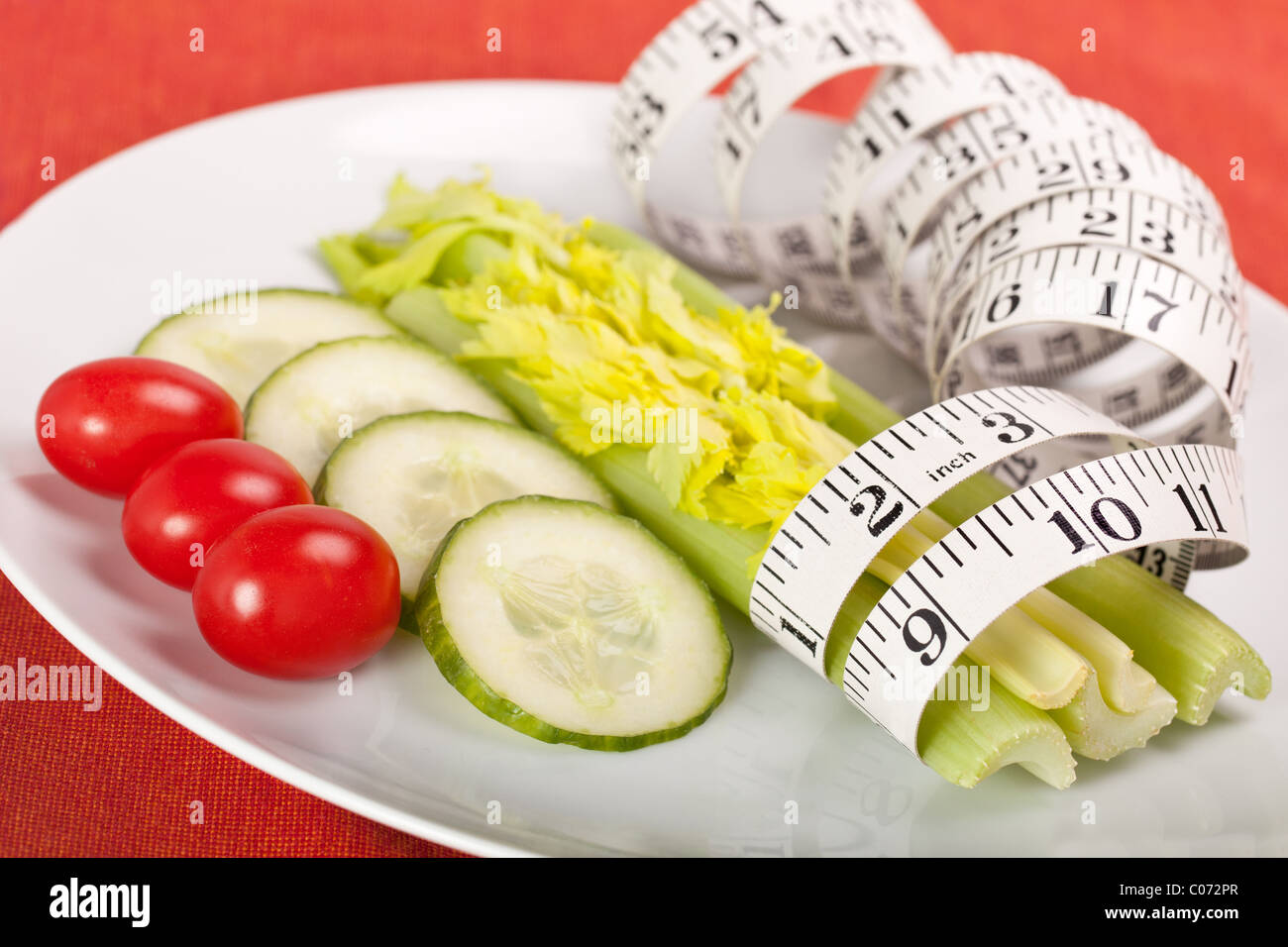 Strict Salad Diet on White Plate with Tape Measure - Stock Image