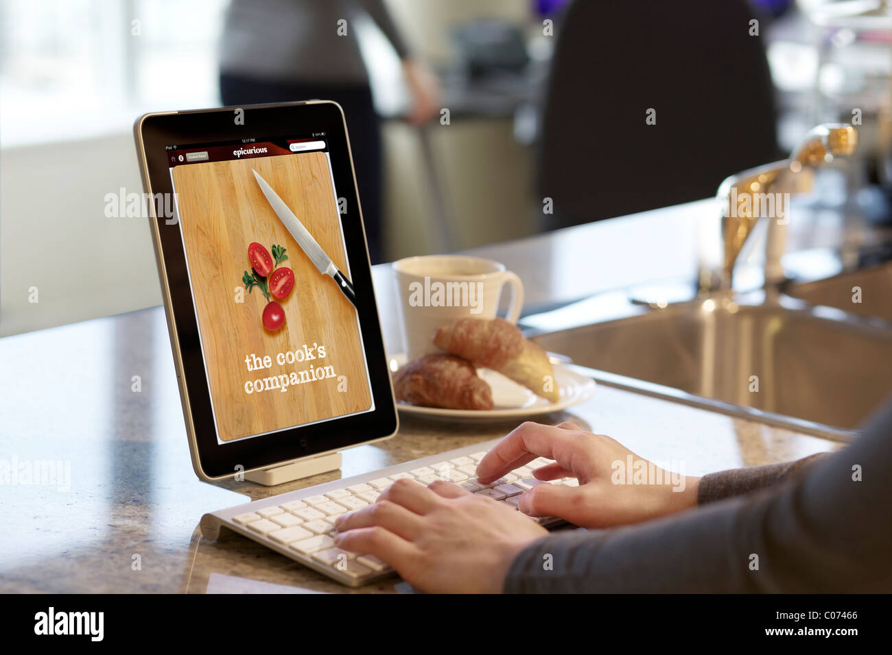 Woman browsing cooking recipe with iPad Epicurious cooking app - Stock Image