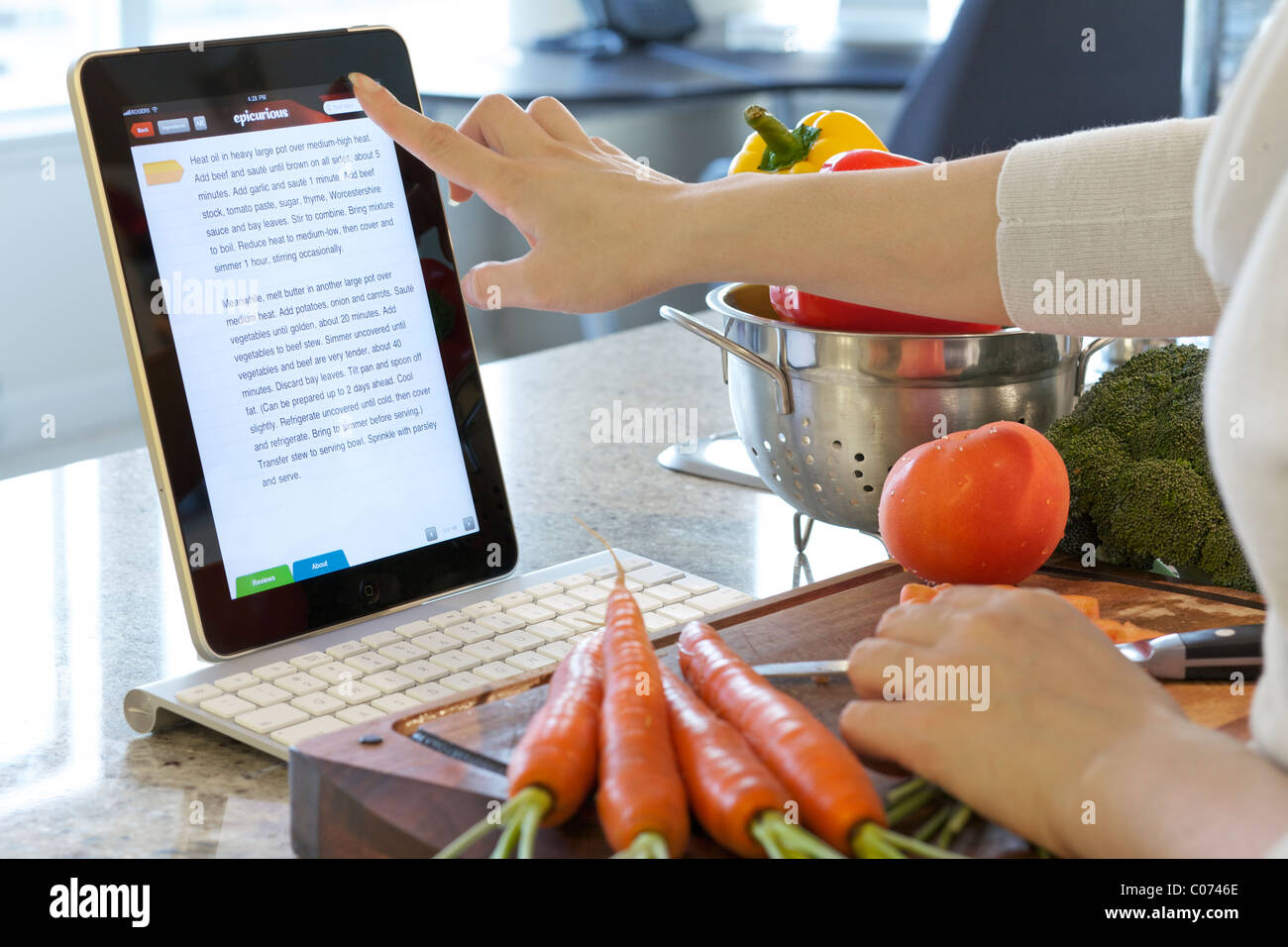 Woman browsing cooking instruction online with Epicurious iPad cooking app - Stock Image