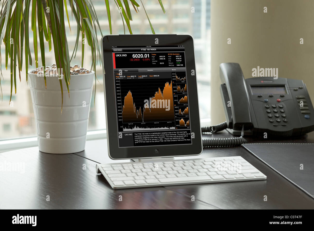 iPad being used in an office with wireless bluetooth keyboard showing Bloomberg app screen - Stock Image