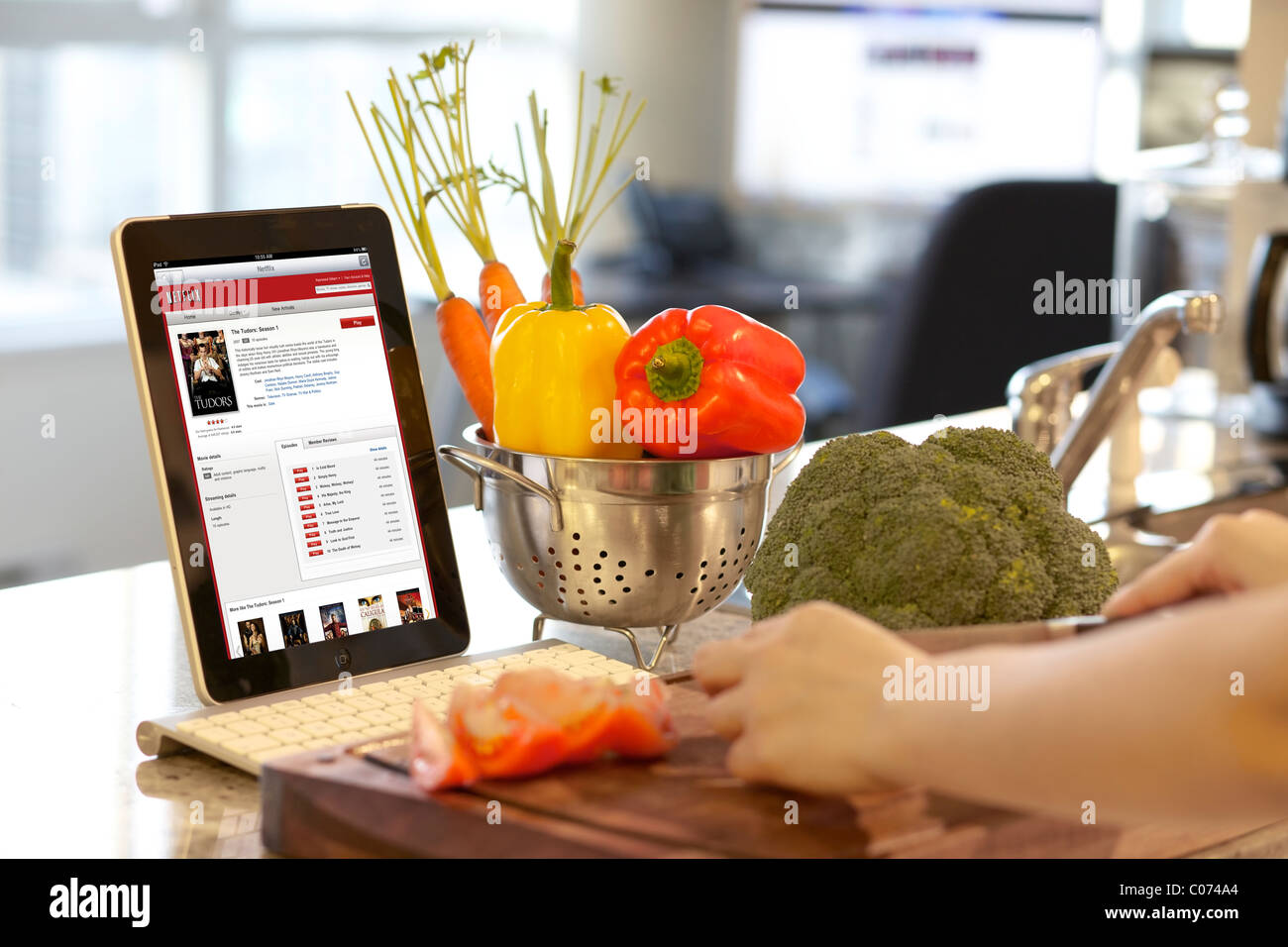 Busy woman cooking in the kitchen while browsing movies on Netflix from her iPad - Stock Image