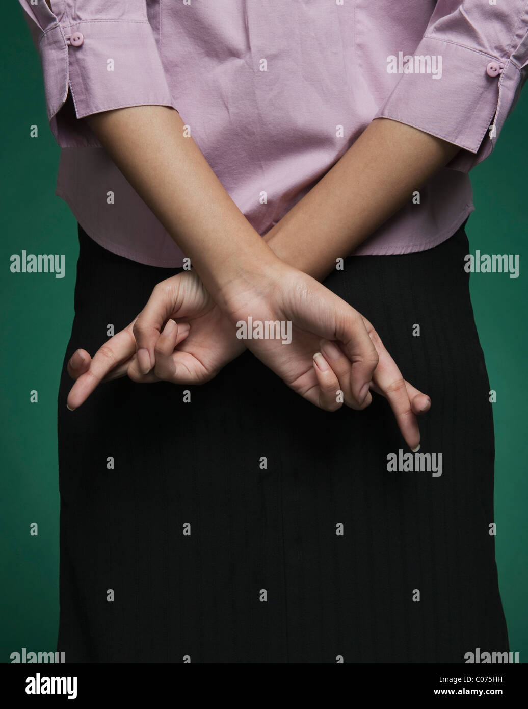 Mid section view of a businesswoman with fingers crossed behind her back - Stock Image