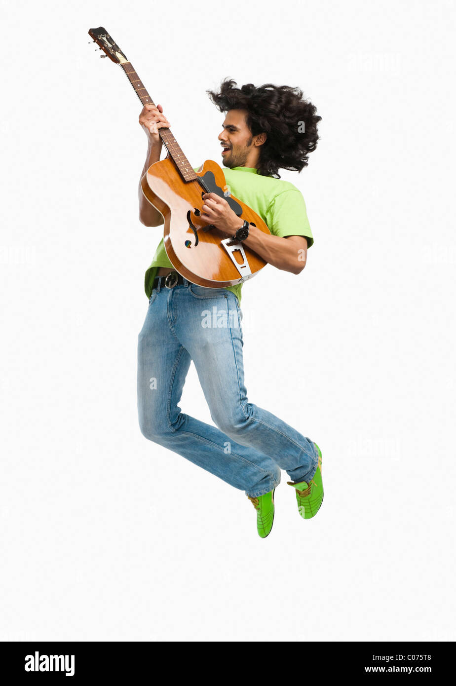 Man jumping in the air while playing a guitar - Stock Image