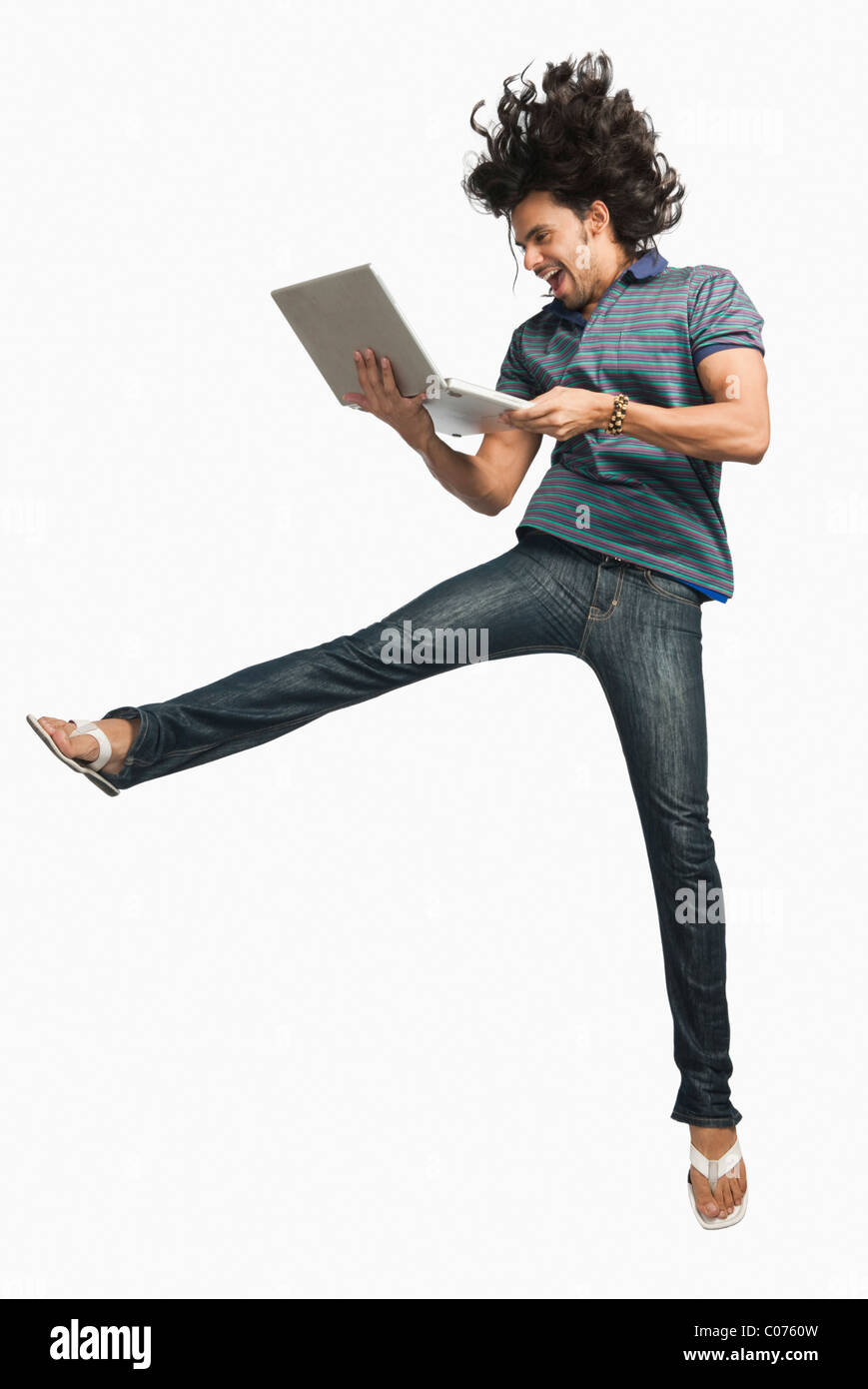 Man jumping while using a laptop - Stock Image
