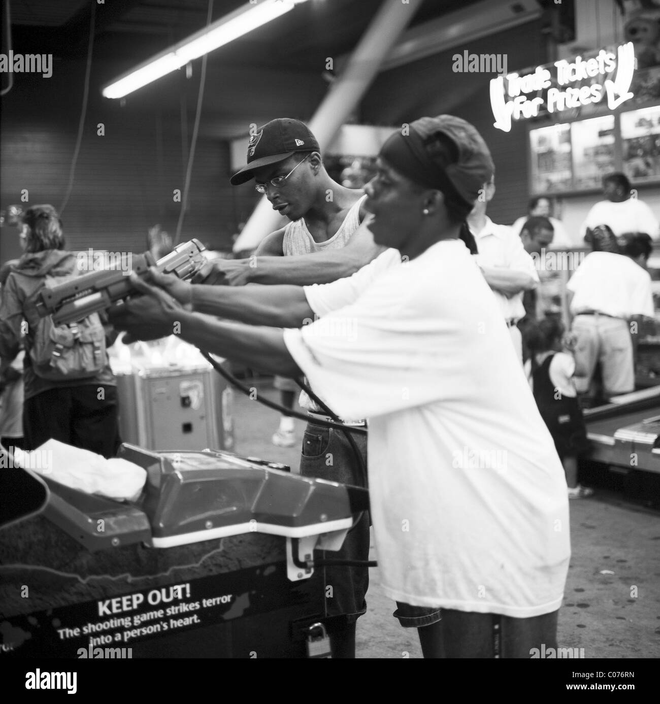 Two black boys playing a shooting game in an arcade, Coney Island, New York, USA - Stock Image