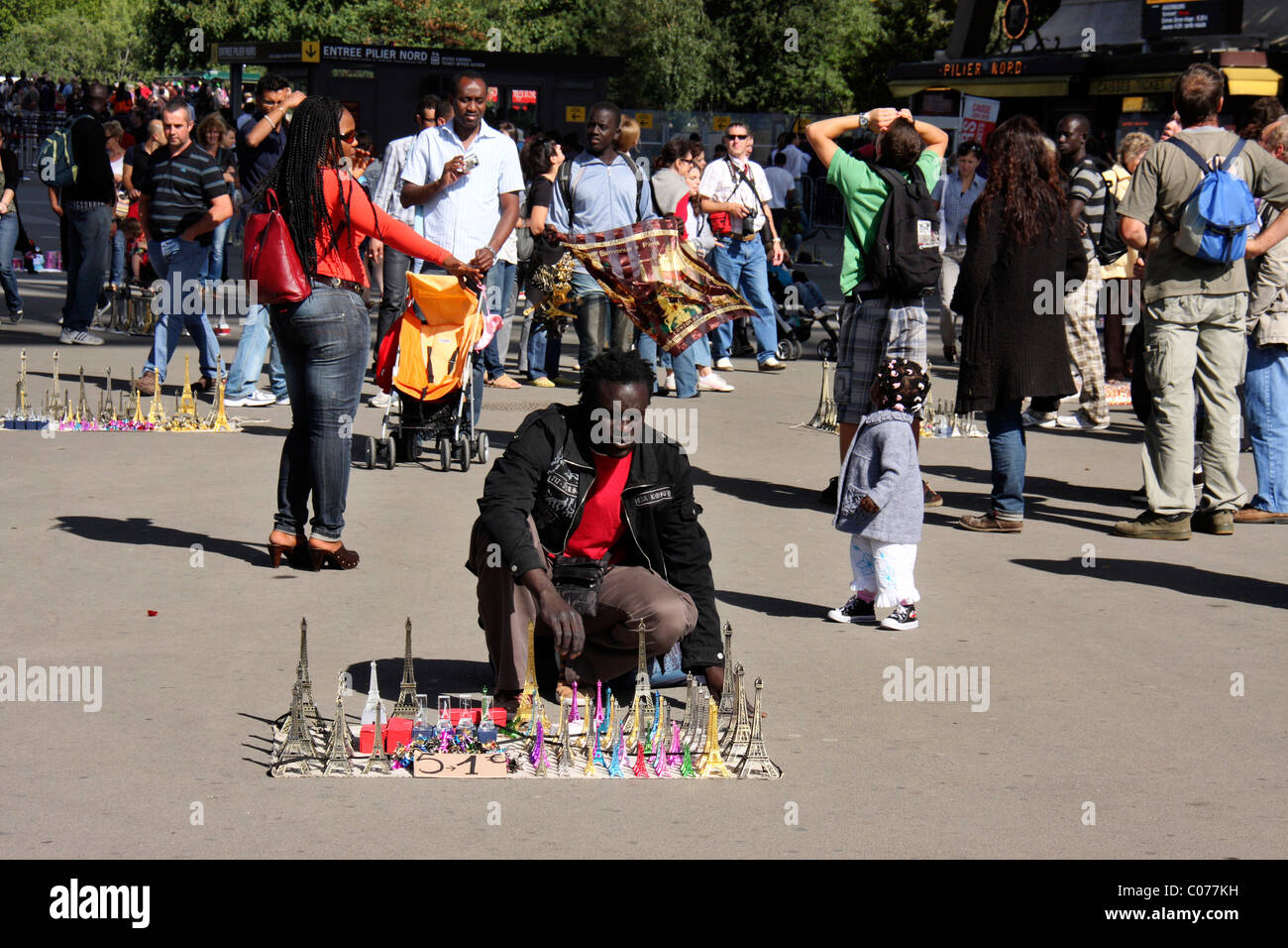 black african migrant man selling eiffel towers souvenirs and curios infront of eiffel towers,paris,france,europe - Stock Image