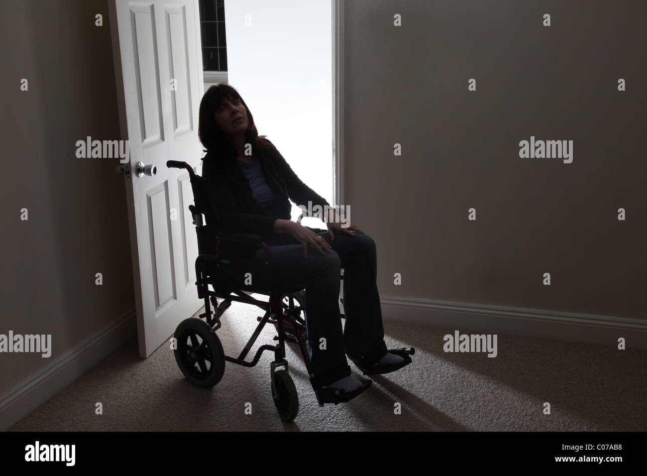 Woman in a wheelchair alone by an open door - Stock Image