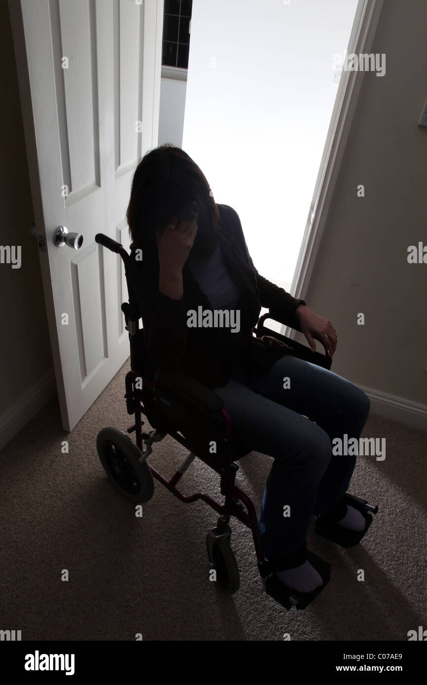 Woman in a wheelchair with hand to her head. - Stock Image