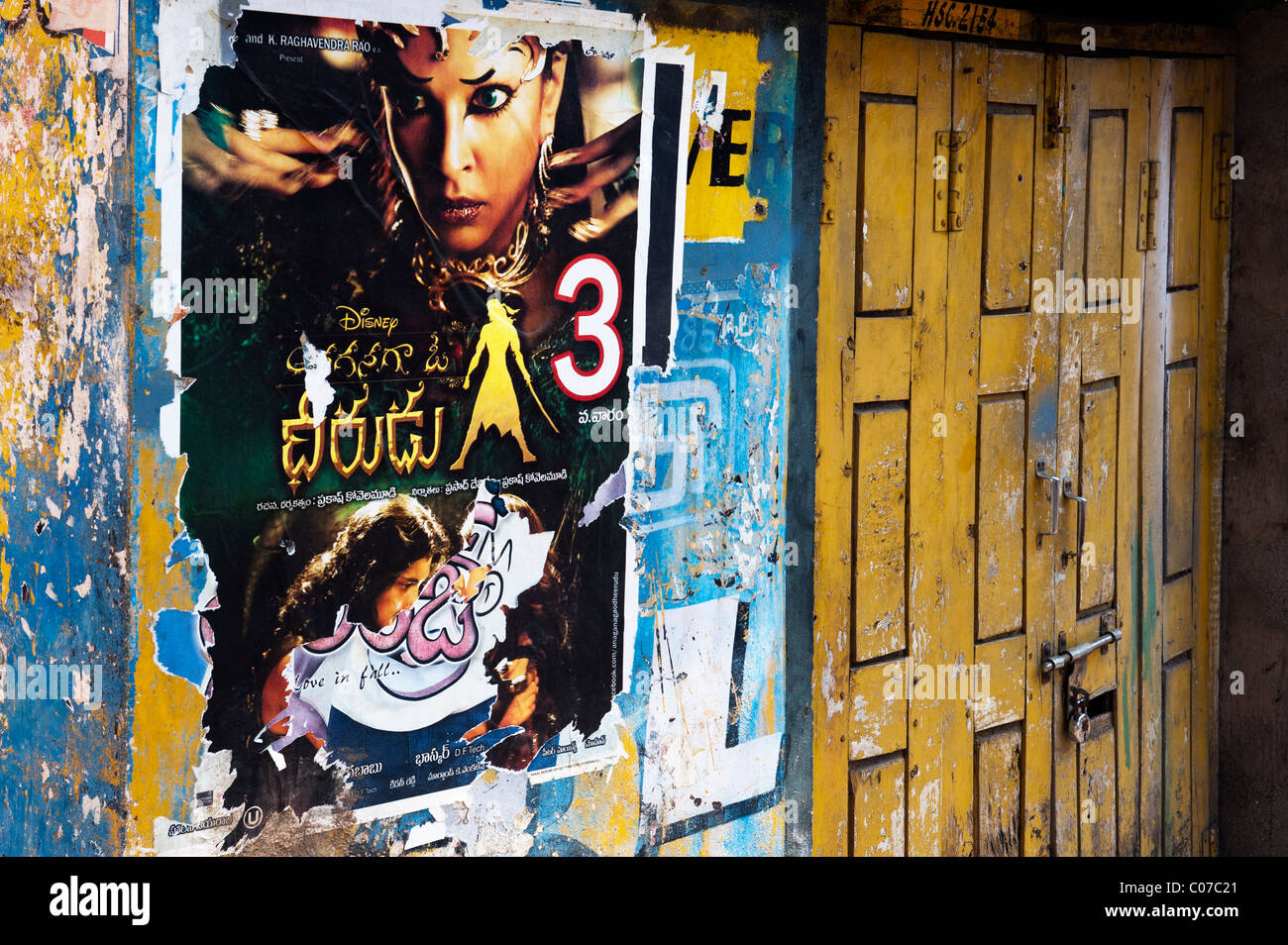 Indian movie posters on a tattered wall of an old rural