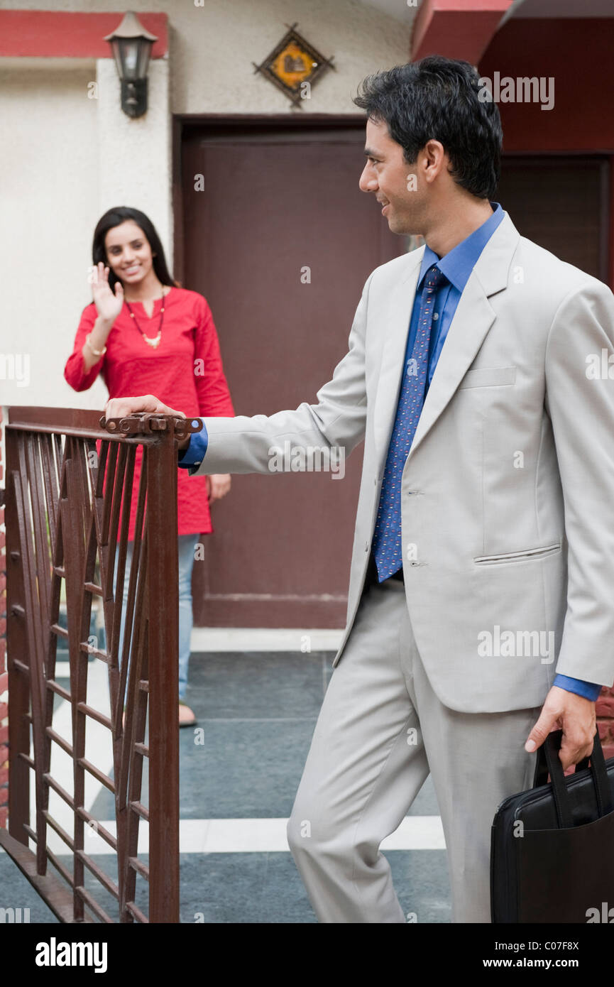 Woman saying goodbye to her husband leaving for office - Stock Image