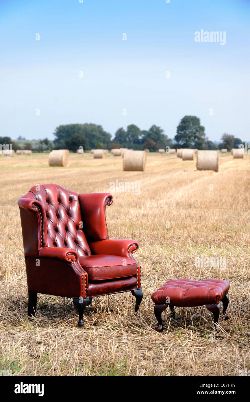 An Antique Red Leather Armchair In A Field Of Harvested Hay