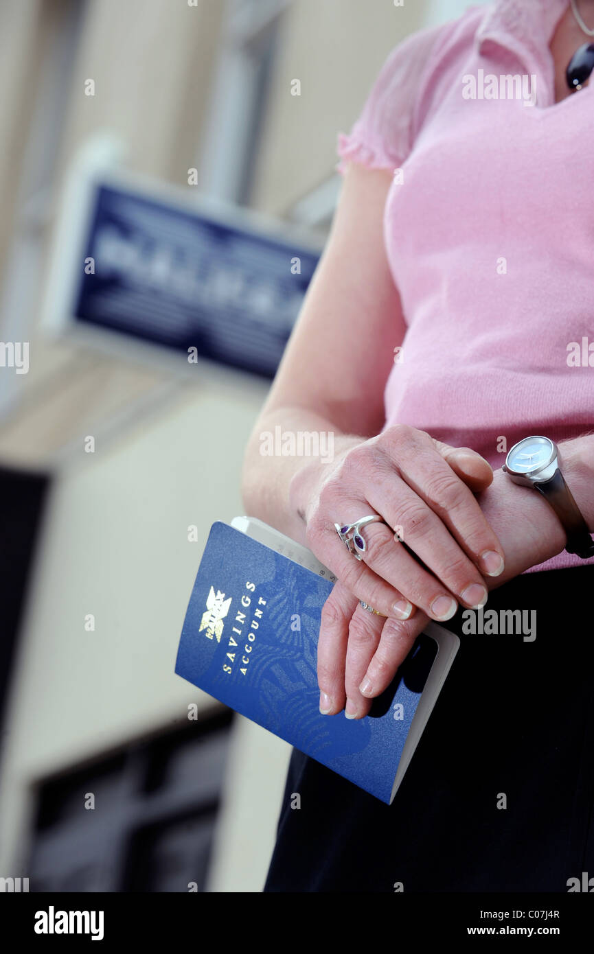 A customer with a traditional savings account pass book outside a branch of the Halifax Bank in Cheltenham UK - Stock Image