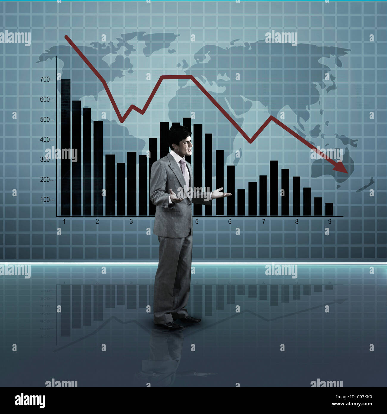 Businessman standing in front of a line graph moving downward - Stock Image