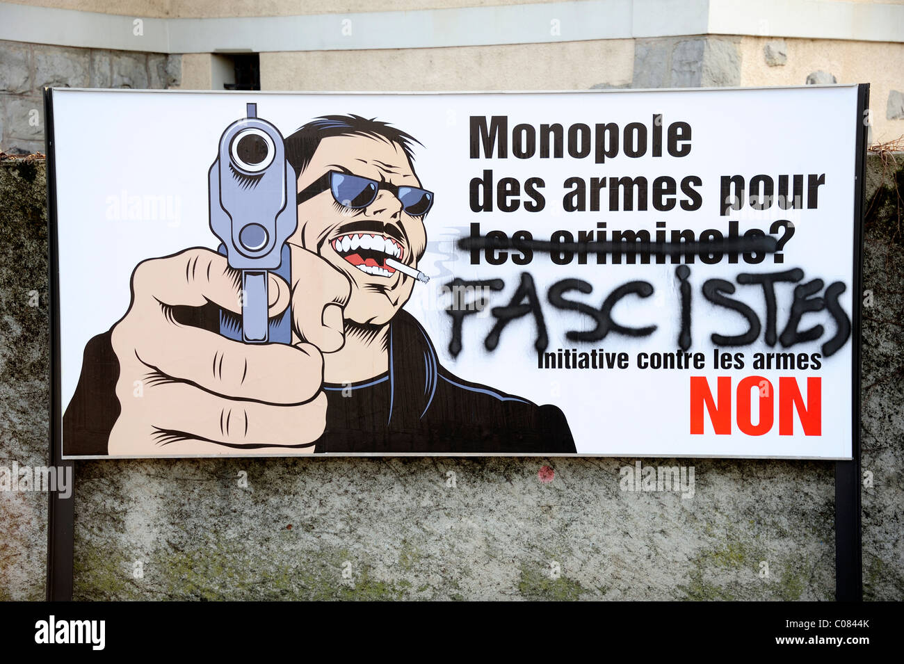 A Swiss right-wing pro-gun poster defaced by left-wing supporters. - Stock Image