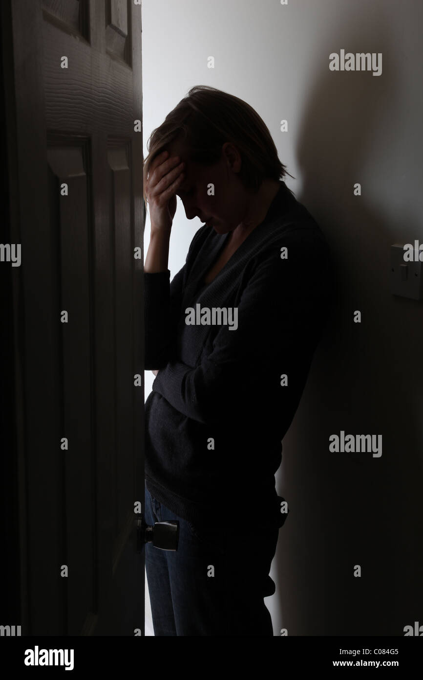 Silhouette of woman, head down hand on head leaning against the wall door slightly open. - Stock Image