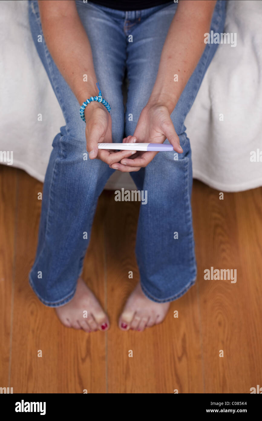 Young woman reading the results of a home test kit for pregnancy - Stock Image