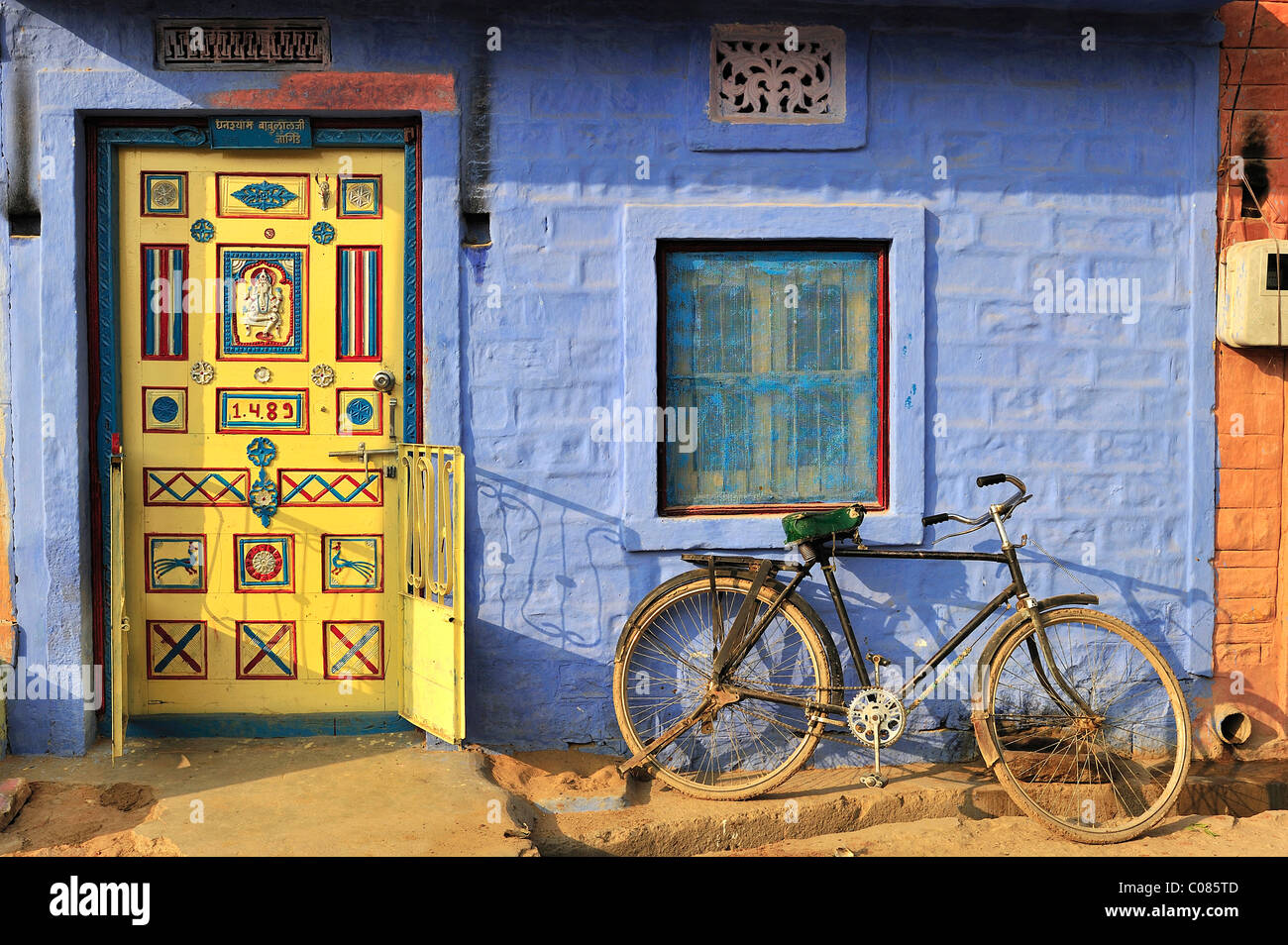 Front Door Decorated With Ornaments And A Bicycle In Front Of A Blue Wall  In An Indian Village, Thar Desert, Rajasthan, India
