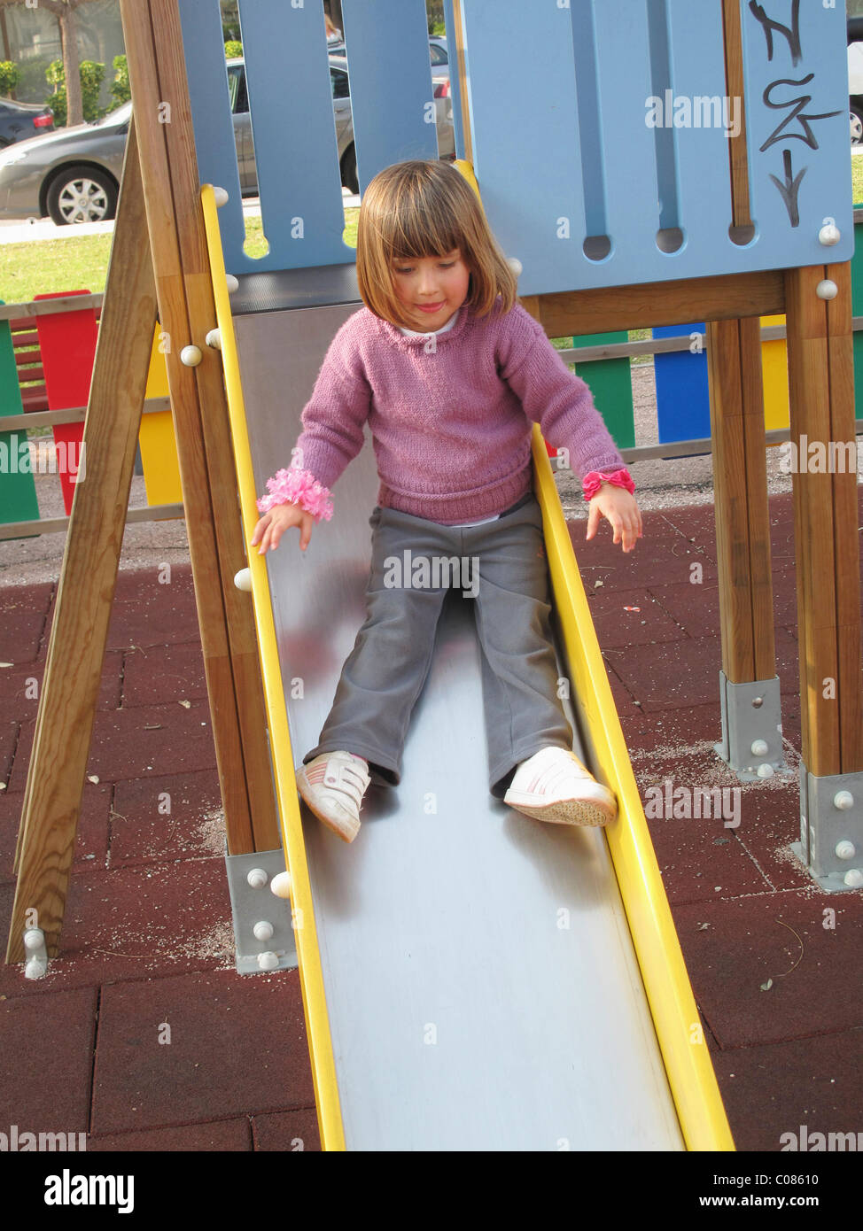 Three and a half year old child on slippery slide in playground Stock Photo