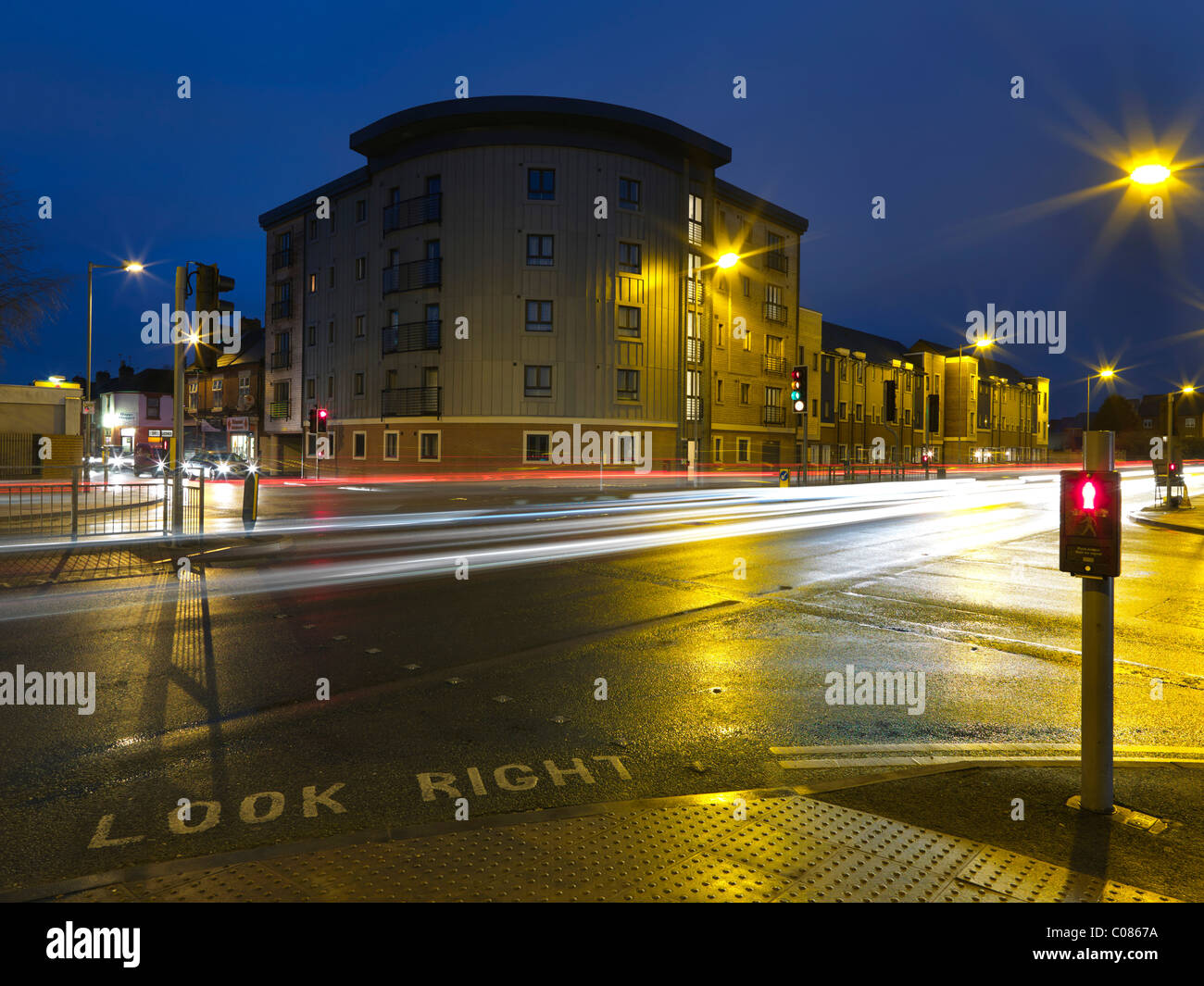 Building at busy road junction at night - Stock Image