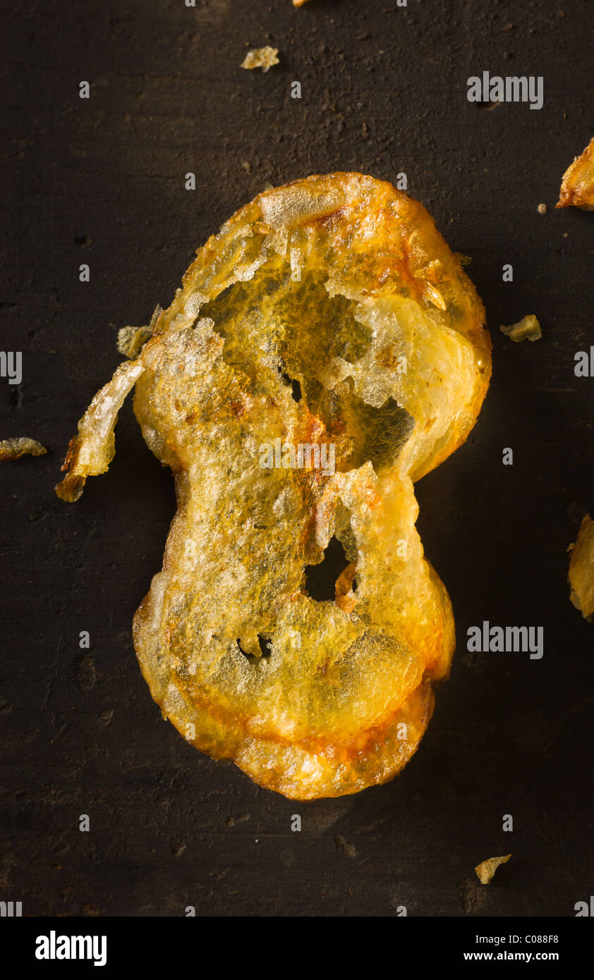Deep Fryed Potato Chips on a dark rustic wood surface - Stock Image